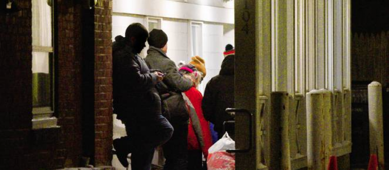 A line of homeless guests in a hallway to enter the Interfaith Winter Shelter on Center Street in Northampton, Massachusetts.